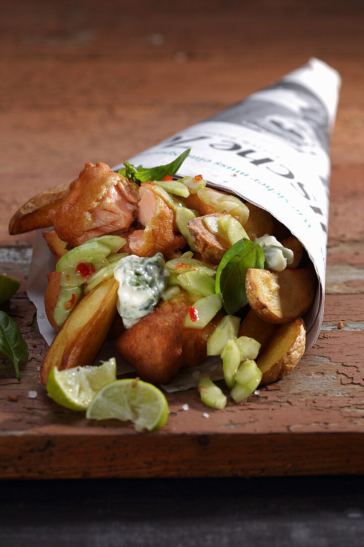 Fish and chips with cucumber and remoulade wrapped in newspaper