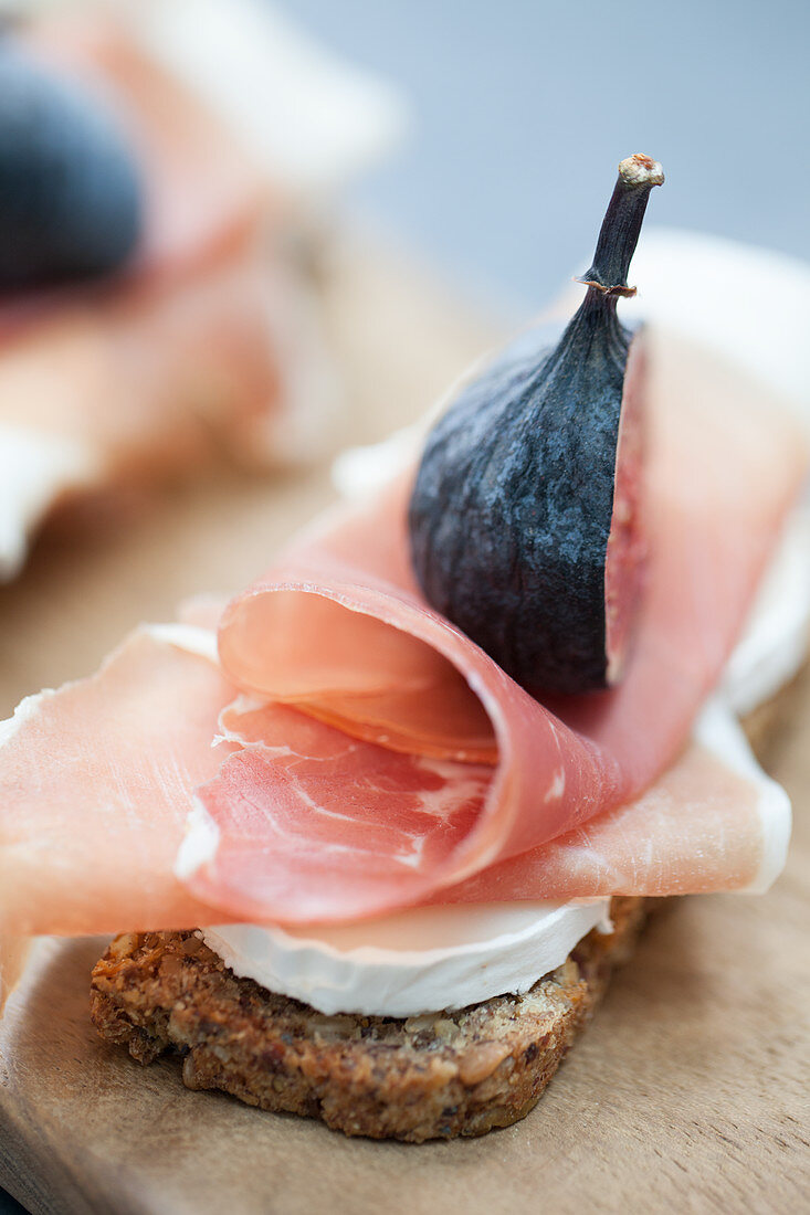A slice of bread topped with goat's cheese, Parma ham and fig