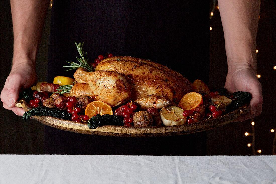 Weihnachtliches Brathähnchen mit Obst und Gemüse servieren