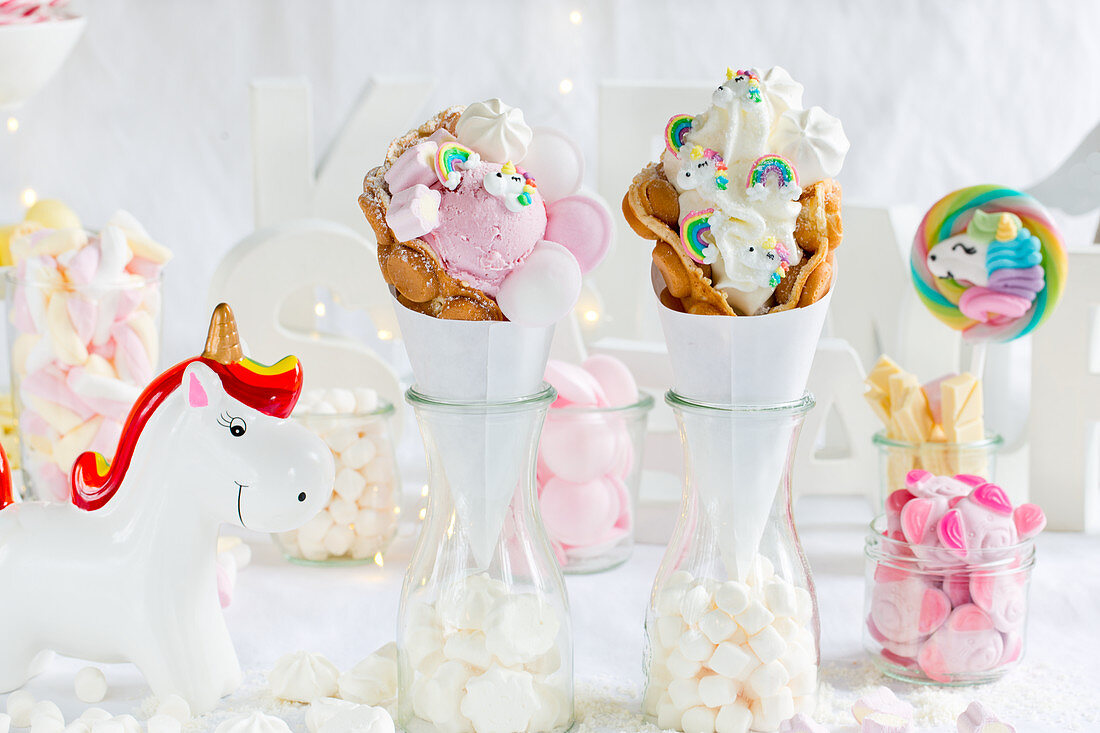 A candy bar table with bubble waffles and unicorn decorations