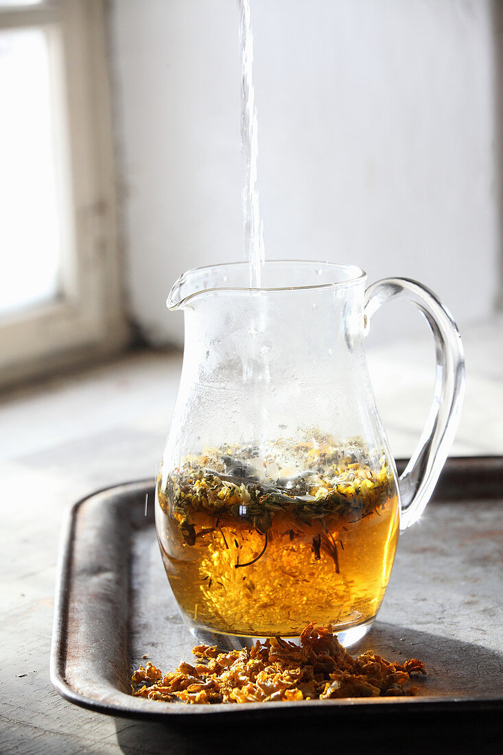 Hot water being added to herbal tea in a glass jug