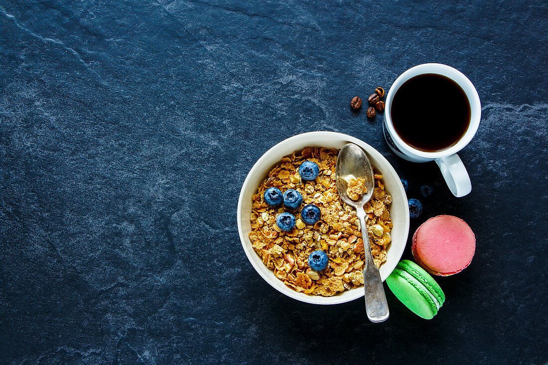 Healthy breakfast of homemade granola in bowl, coffee in white cup, berries and macaroons