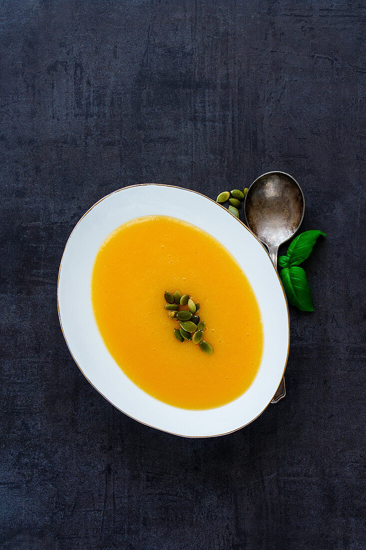 Traditional pumpkin cream soup in white bowl with fresh green basil leaves, spices and pumpkin seeds on dark vintage stone background