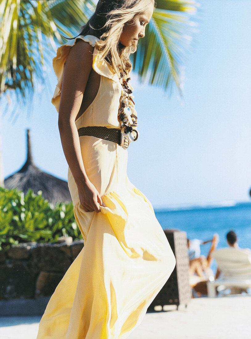 Junge Frau in langem, gelbem Kleid am Strand