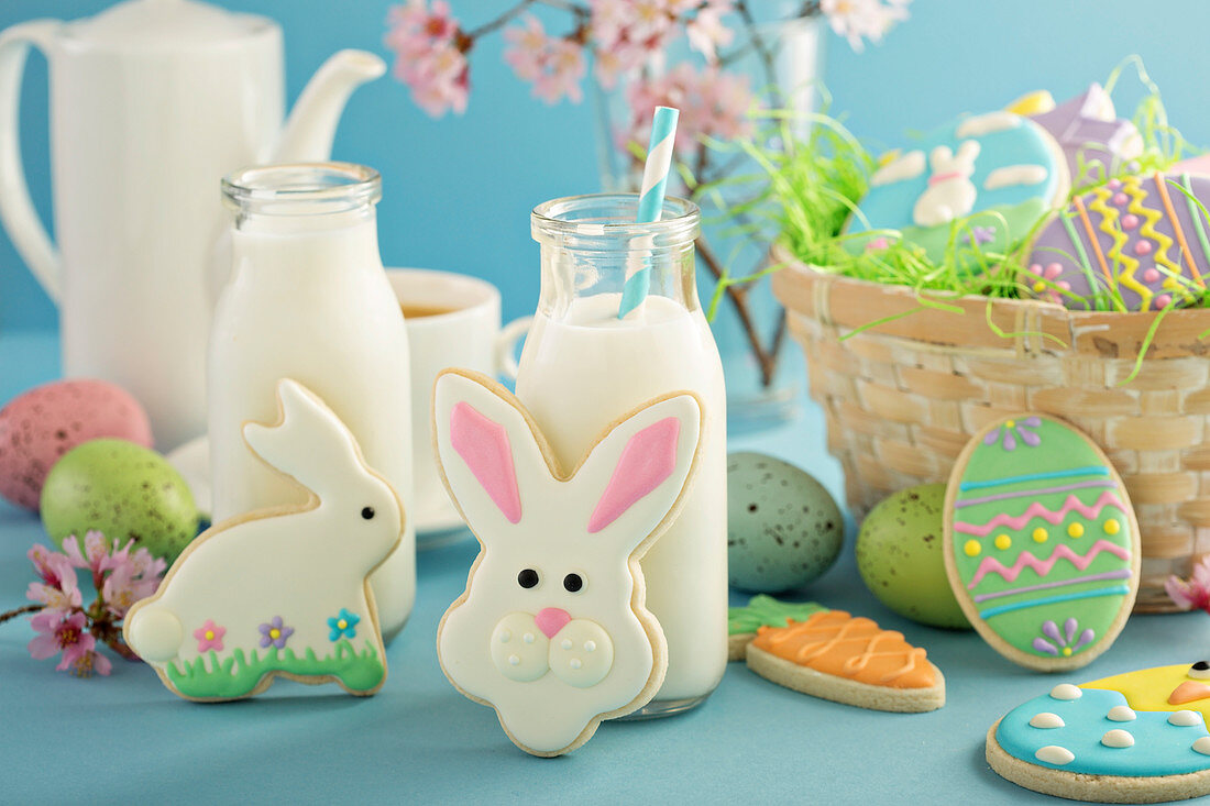 Easter cookies on blue table with milk in little bottles