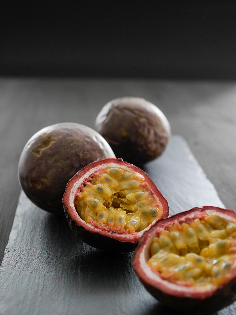 Passion fruit, whole and halved, on a slate platter