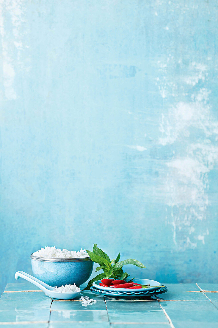 A bowl of rice and a plate of chillies and fresh mint against a blue background