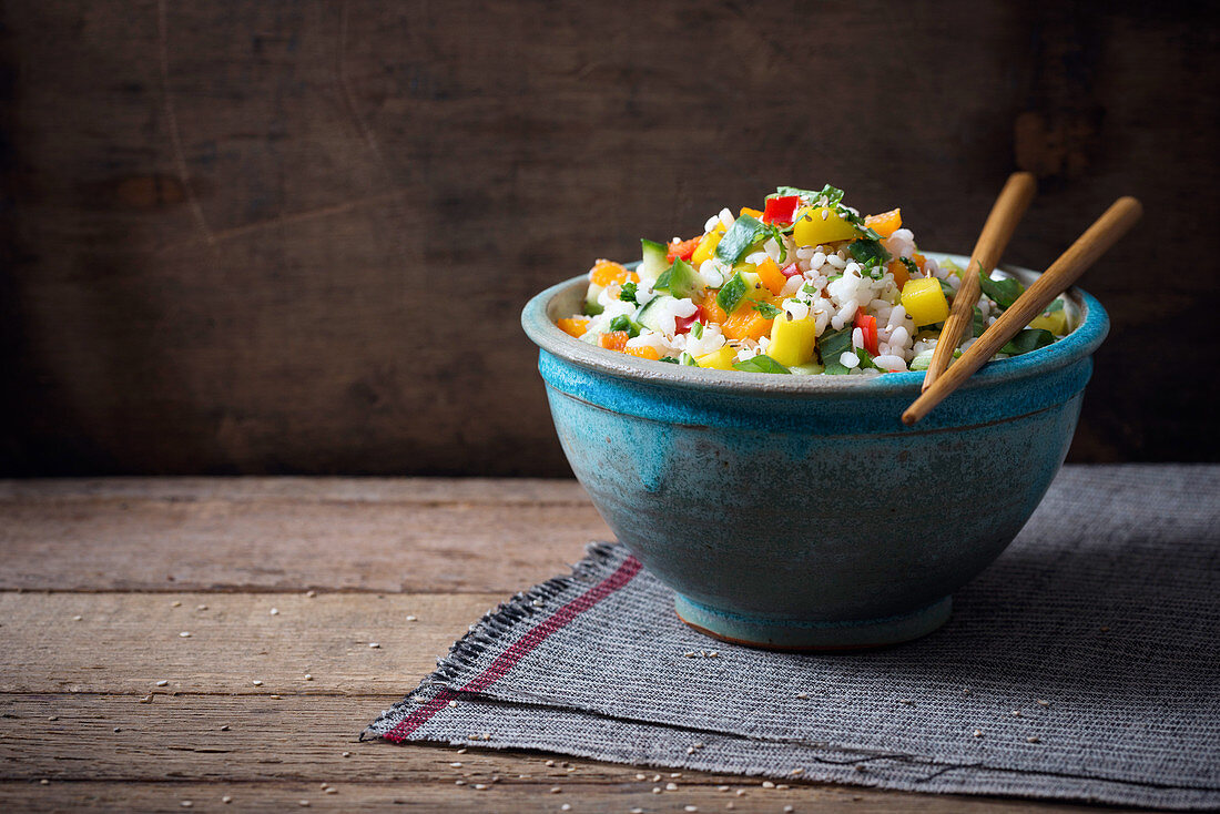 A vegen rice salad with mango, peppers, cucumber, bok choy and sesame seeds (Asia)