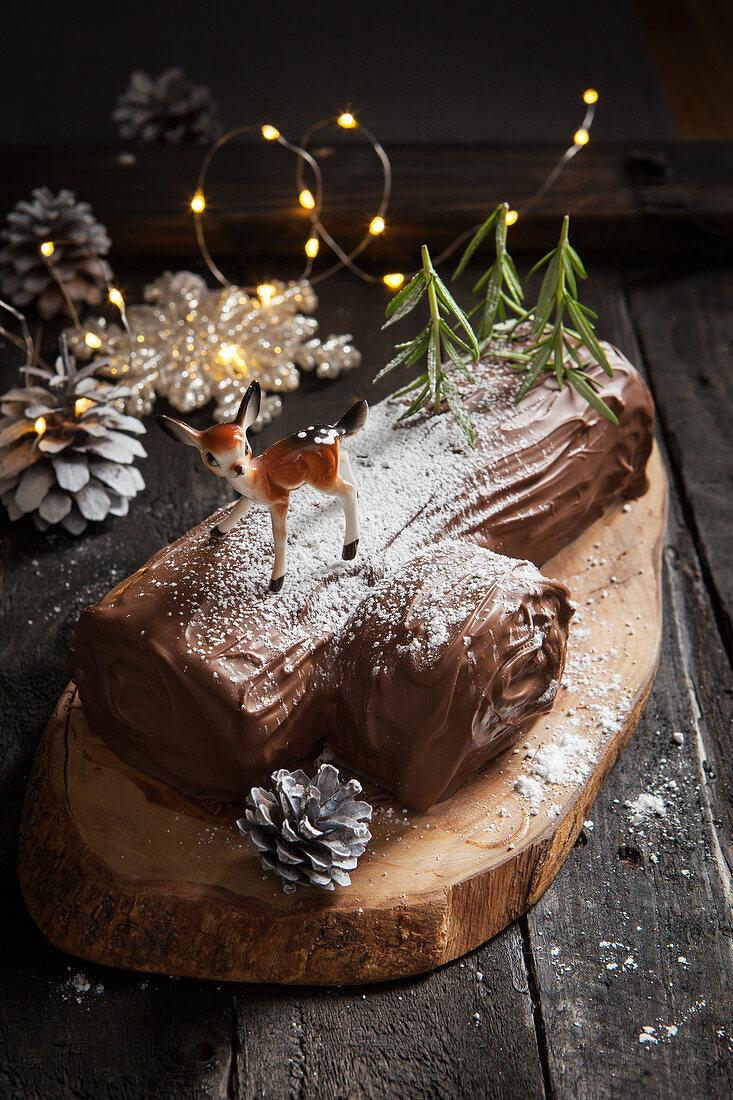 A yule log (Christmas chocolate roll) on a wood slice