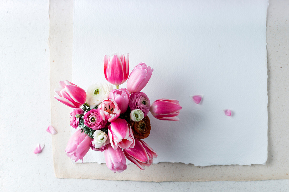 Spring bouquet of pink tulips and ranunculus (top view)