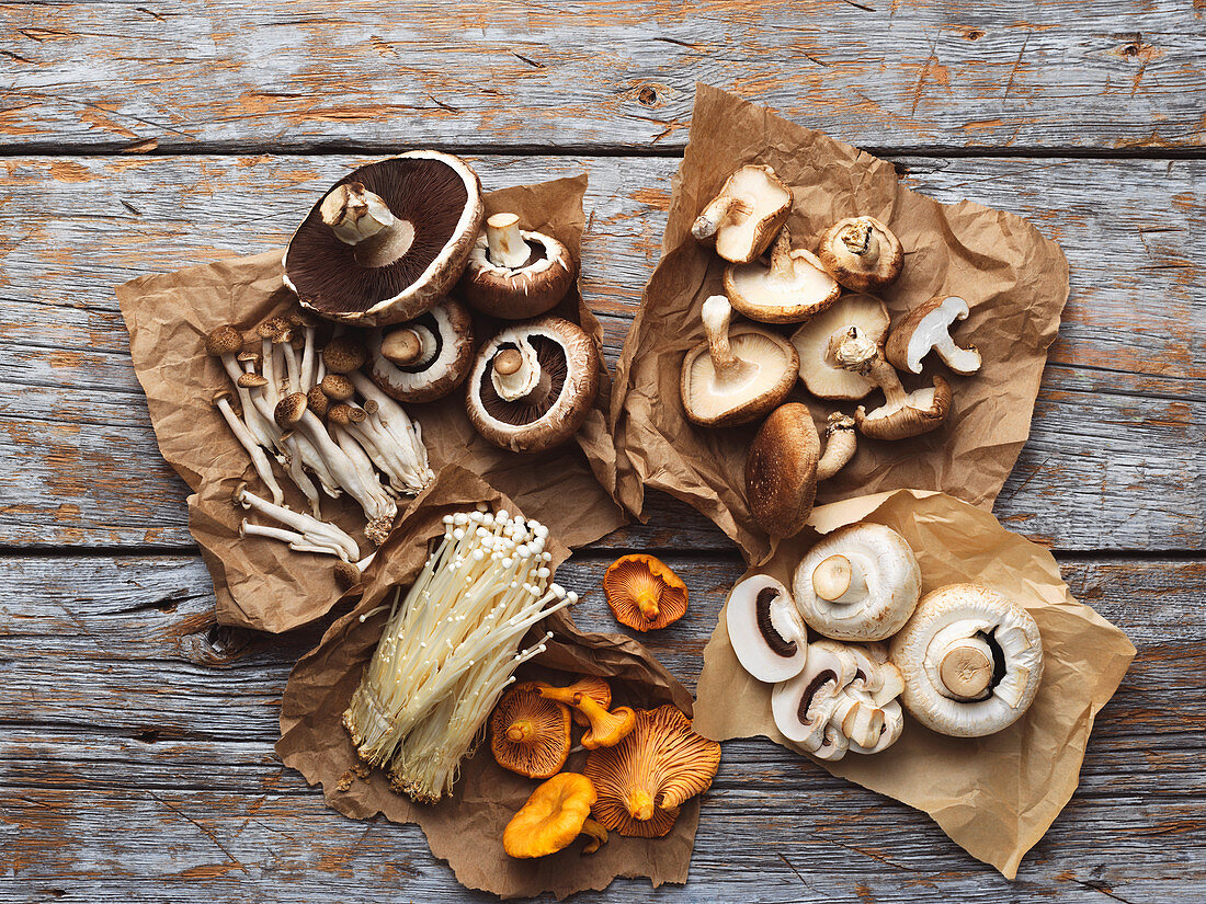 Various types of mushrooms on paper against a wooden background (top view)