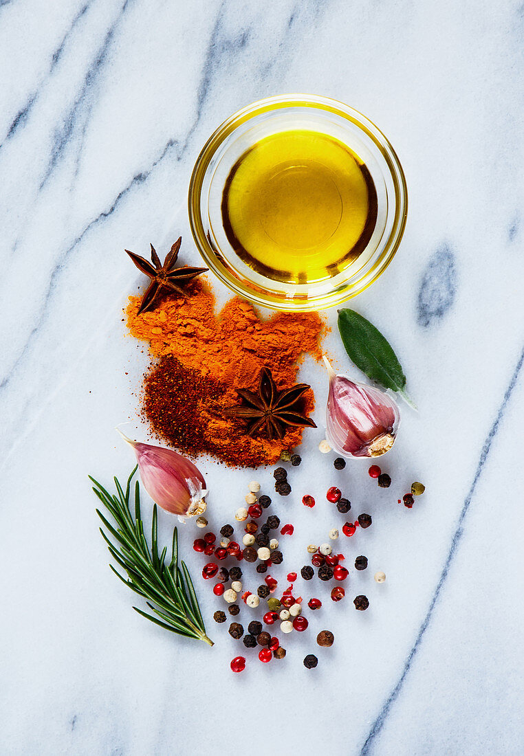 Olive oil and bright spices (curry, paprika, garlic, rosemary, pepper) on marbre background