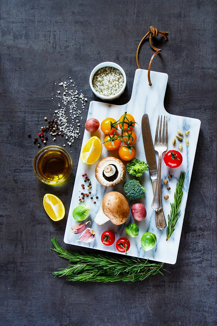 Colorful vegetables and spices on marbre cutting board. Bio Healthy food, herbs and spices
