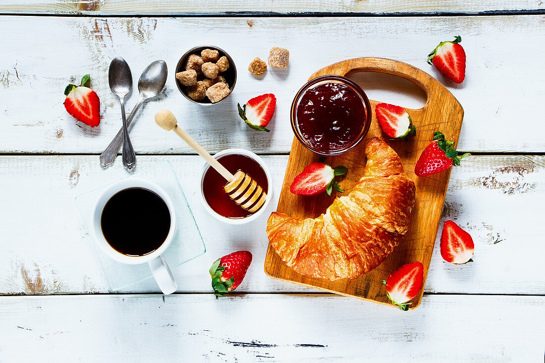 Rural breakfast with fresh croissant, cup of coffee, fruity jam, honey and strawberries on rustic white wooden background