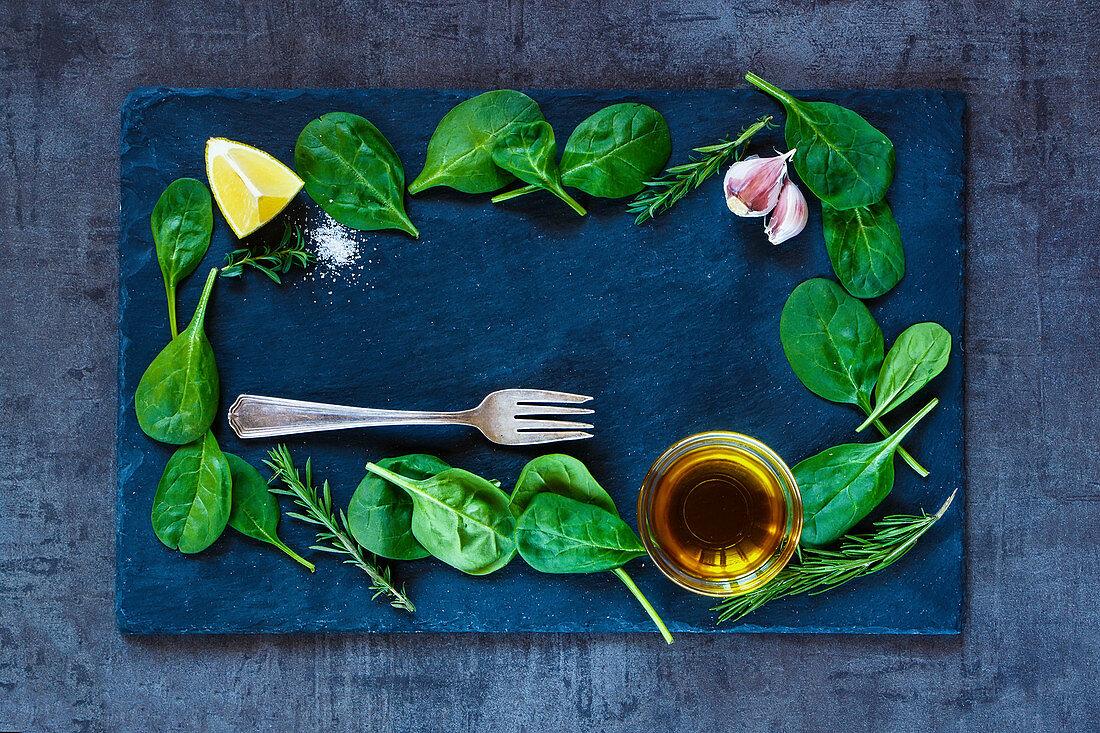 Babyspinatsblätter und Olivenöl auf Schieferplatte