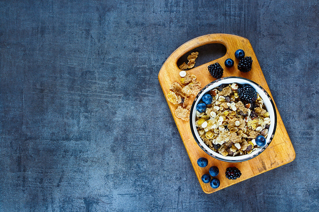 Top view of deliciousl breakfast table with granola in vintage bowl and fresh dark berries on grunge background