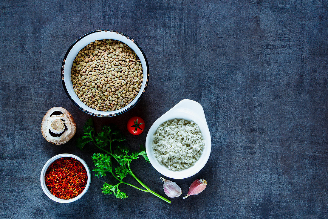 Green lentils with various colorful spices and vegetables on dark grunge table