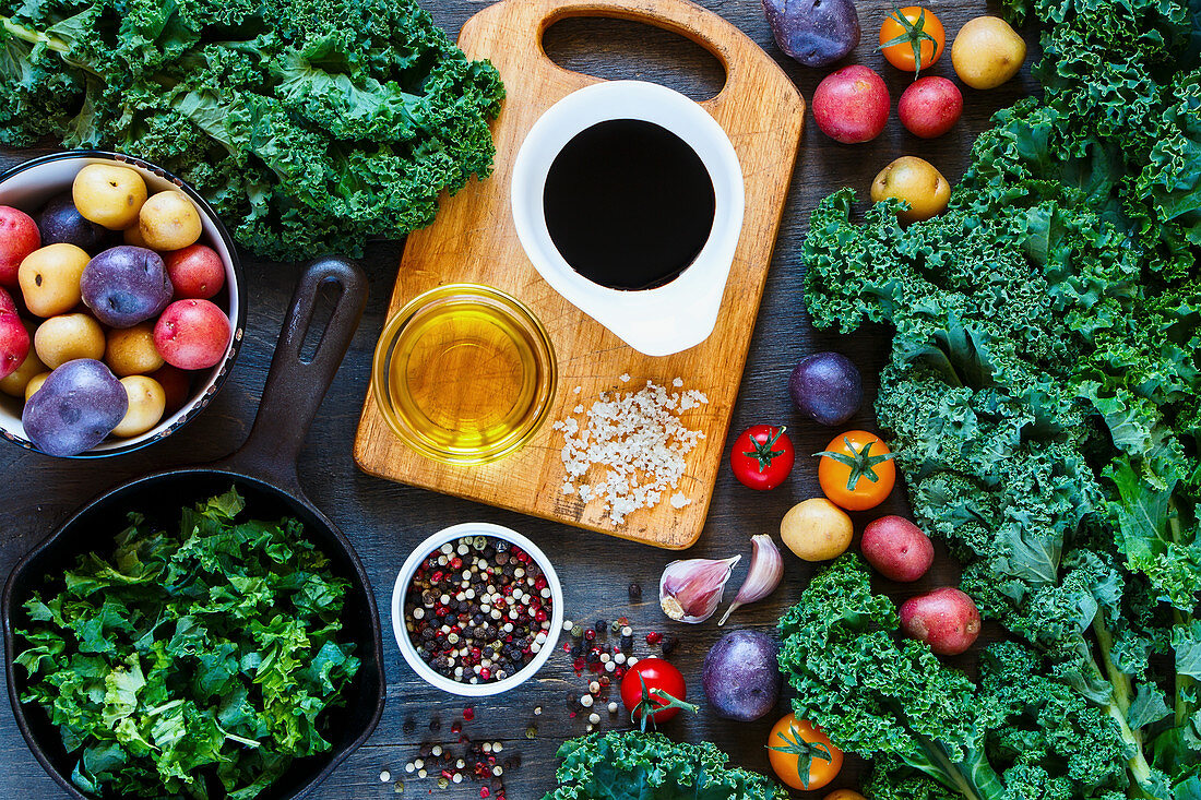 Vegetarian food background with old cutting board, cast iron skillet and fresh colorful organic vegetables