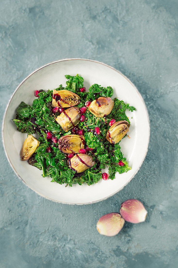 Warm roasted kale salad with baby artichokes and balsamic pomegranate cream (vegan)