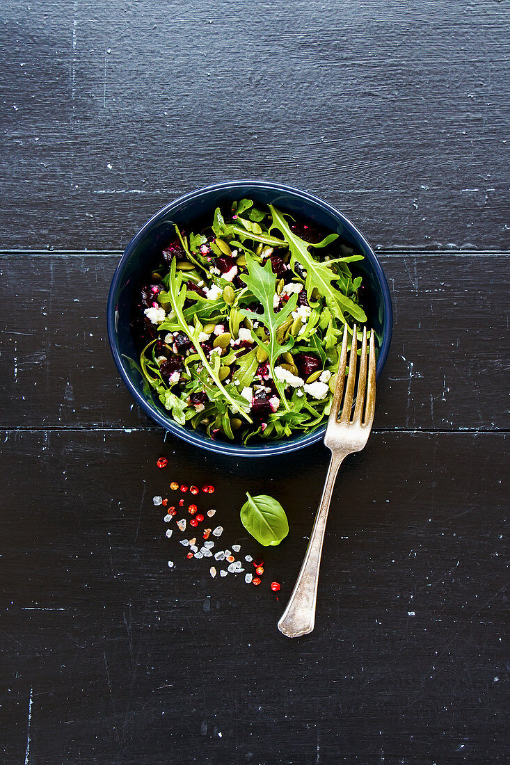 Vegetarian beetroot, arugula, feta cheese and pumpkin seed salad in black ceramic plate