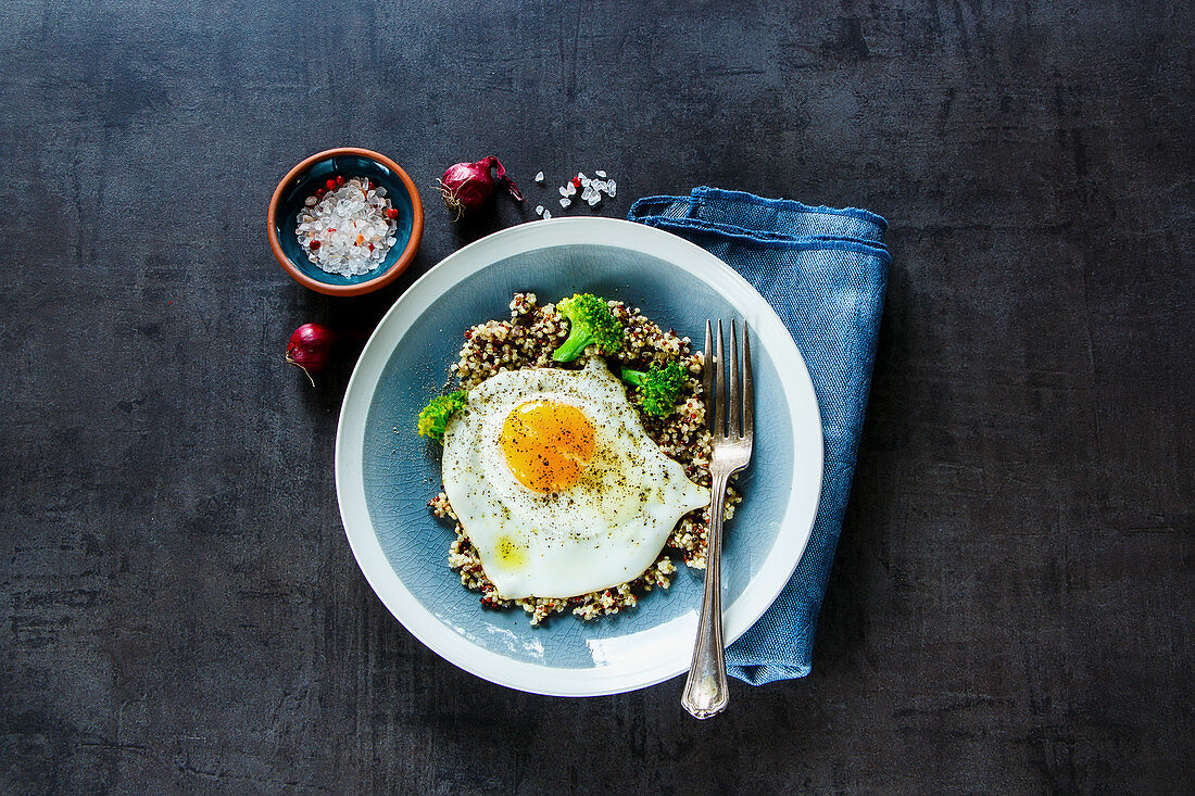 Quinoa, broccoli and egg over dark concrete background