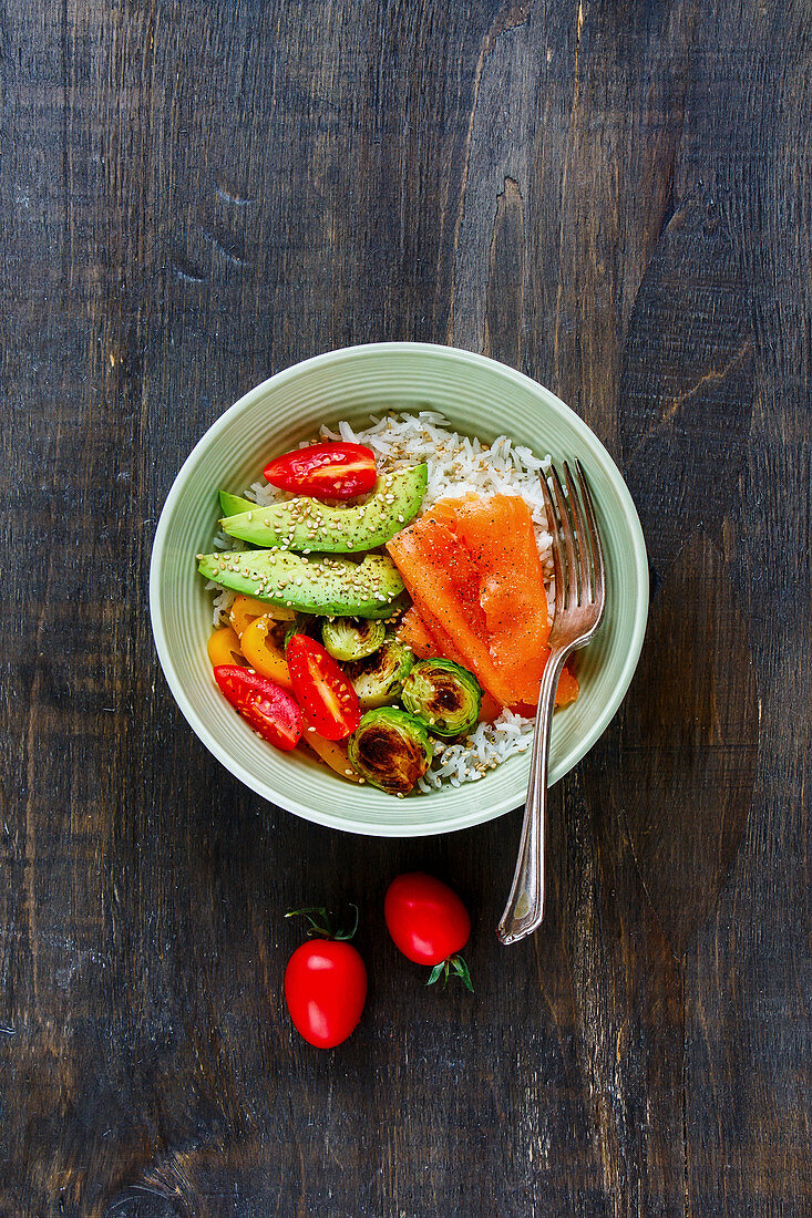 Buddha Bowl with avocado, tomatoes, brussel sprouts, rice, smoked salmon