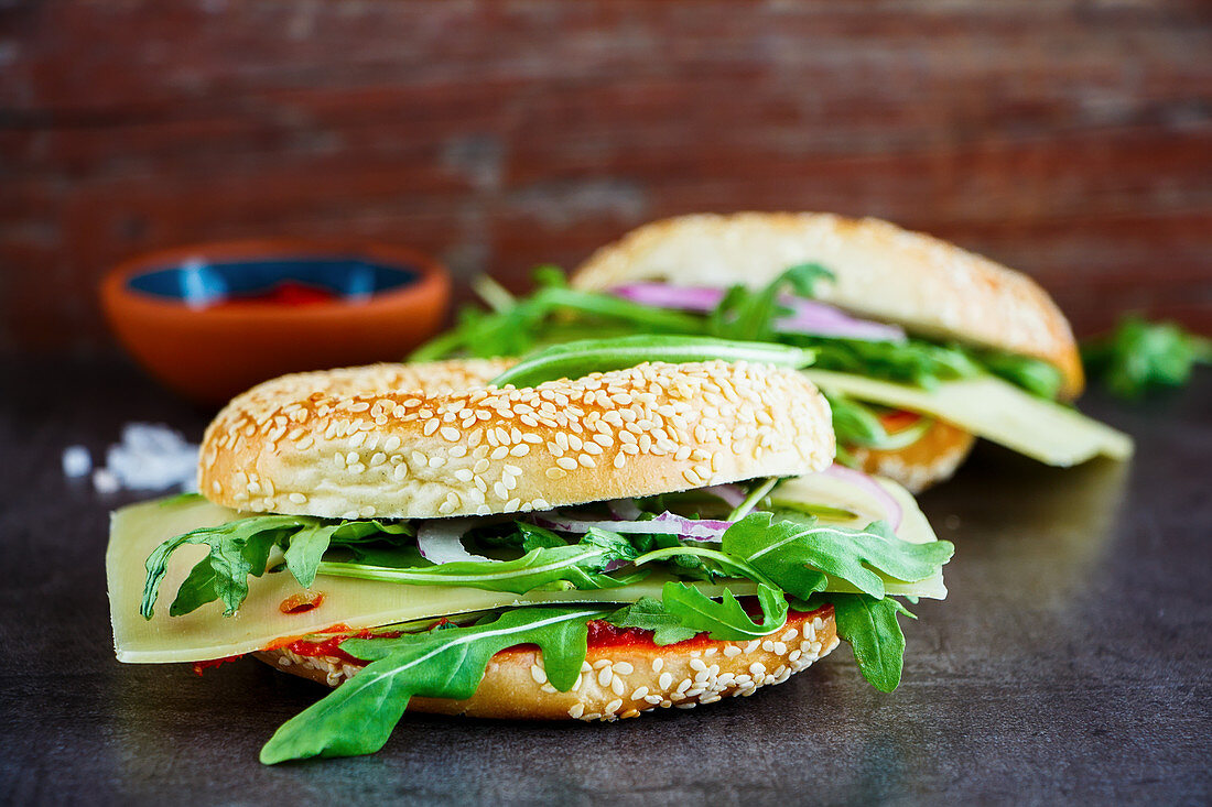 Healthy cheeseburger made of fresh seeded bagel, cheese, tomato sauce, arugula and onion on stone background