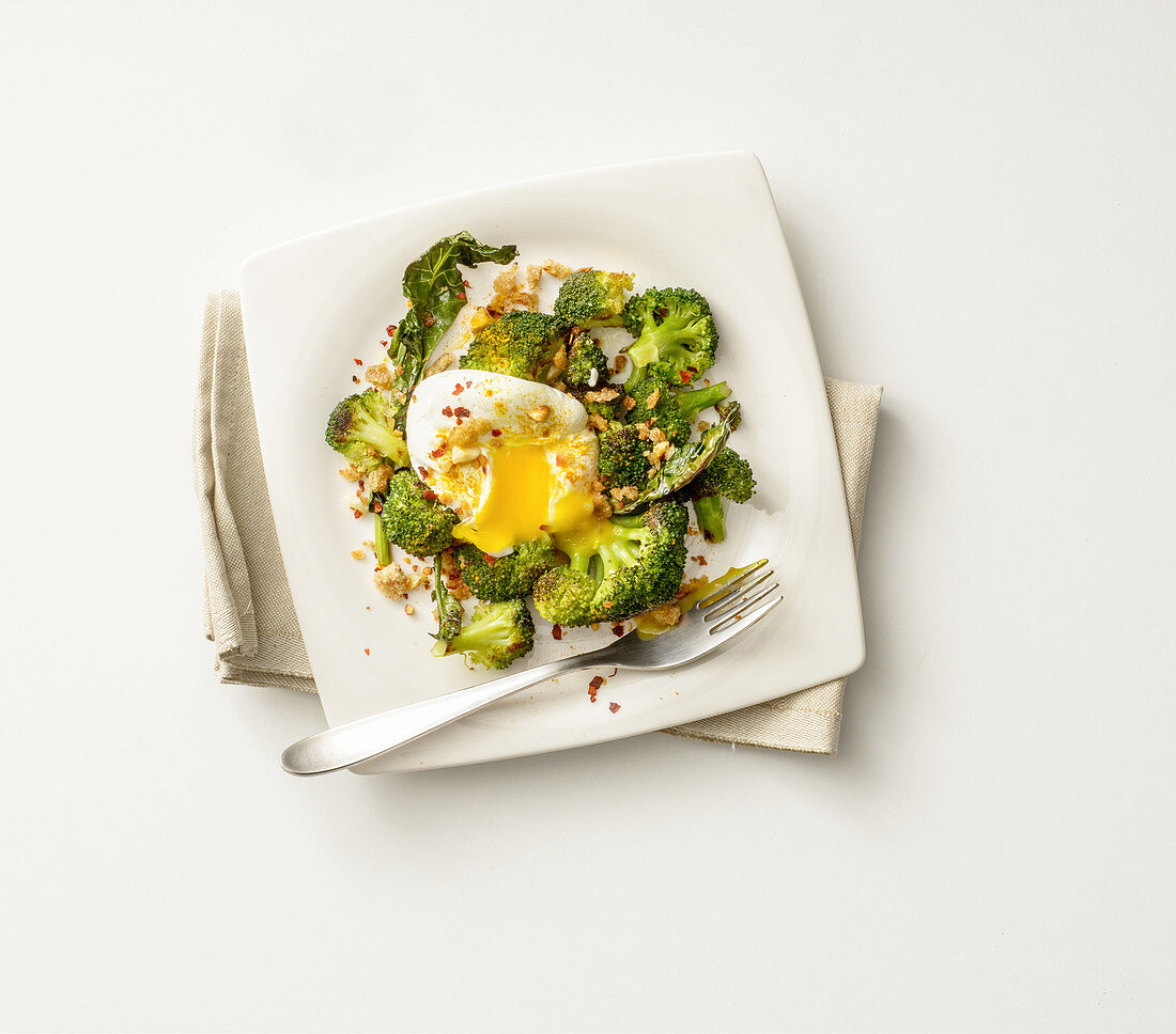 A poached egg and broccoli with chopped almonds