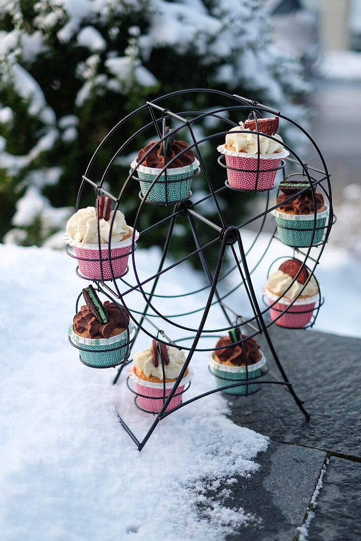 Various cupcakes on a cake stand in the snow