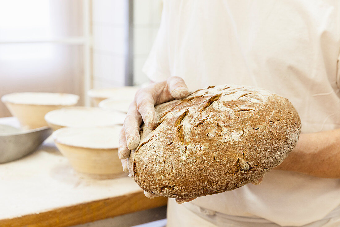 A baker holding a freshly baked loaf of bread