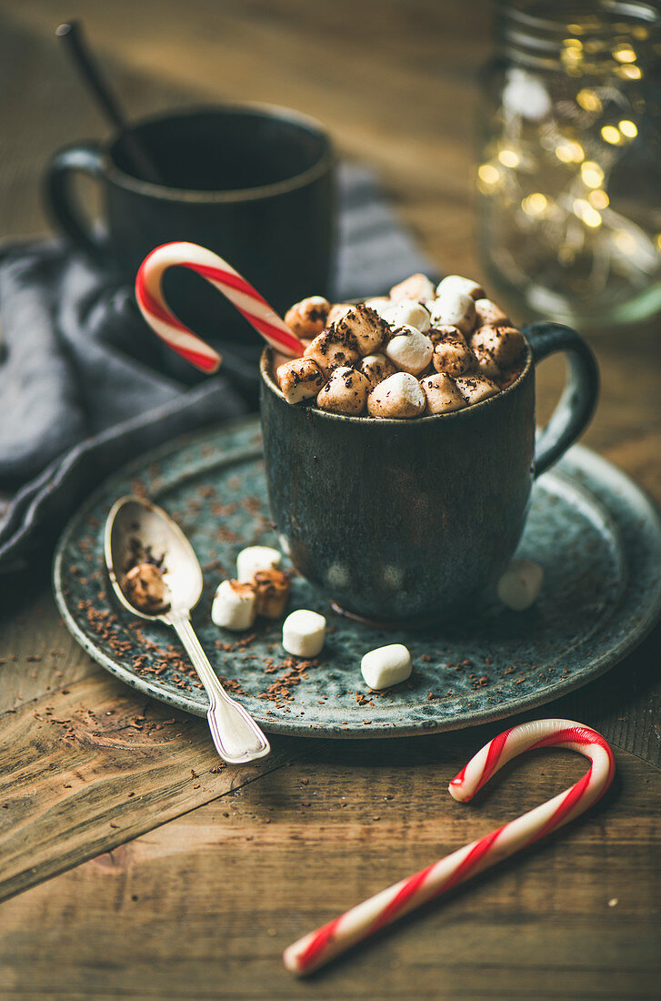 Winter warming sweet drink hot chocolate with marshmallows and cocoa in mug with candy cane