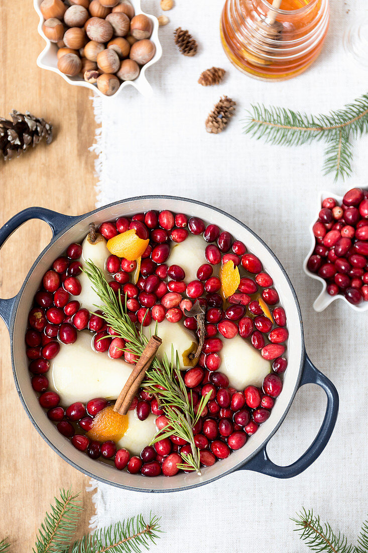 Poached pears with cranberries, cinnamon, rosemary and orange peel in a pot