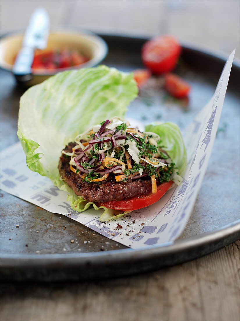 A meatball with tomato slices in a lettuce leaf