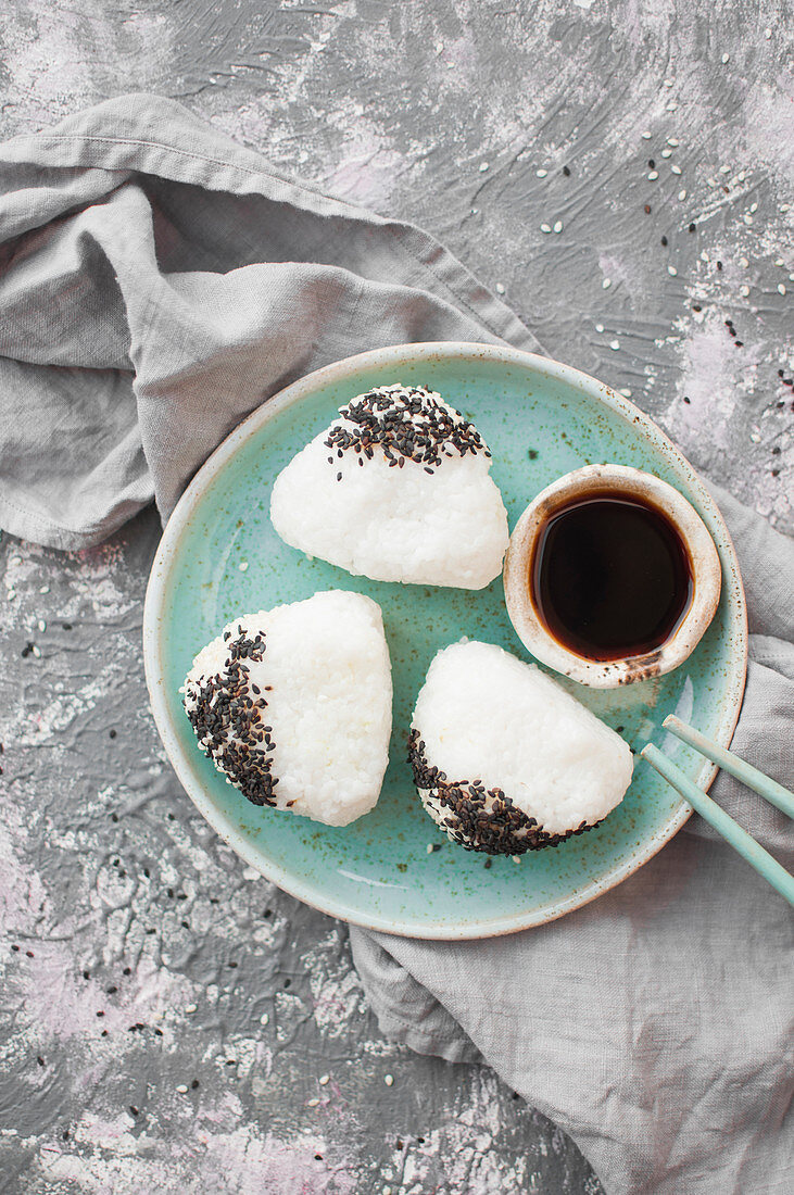 Onigiri with wasabi and avocado, served with soy sauce, Japanese rice sandwich