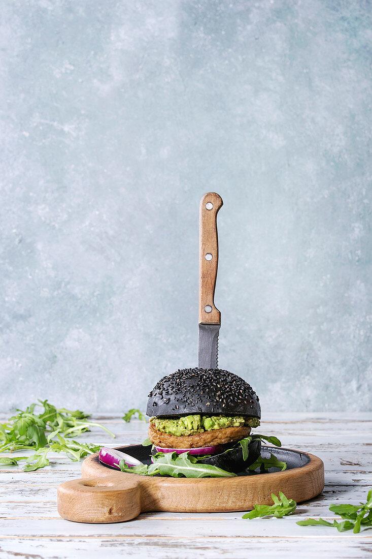 Homemade burger in black bun with avocado, arugula, onion on wood serving board