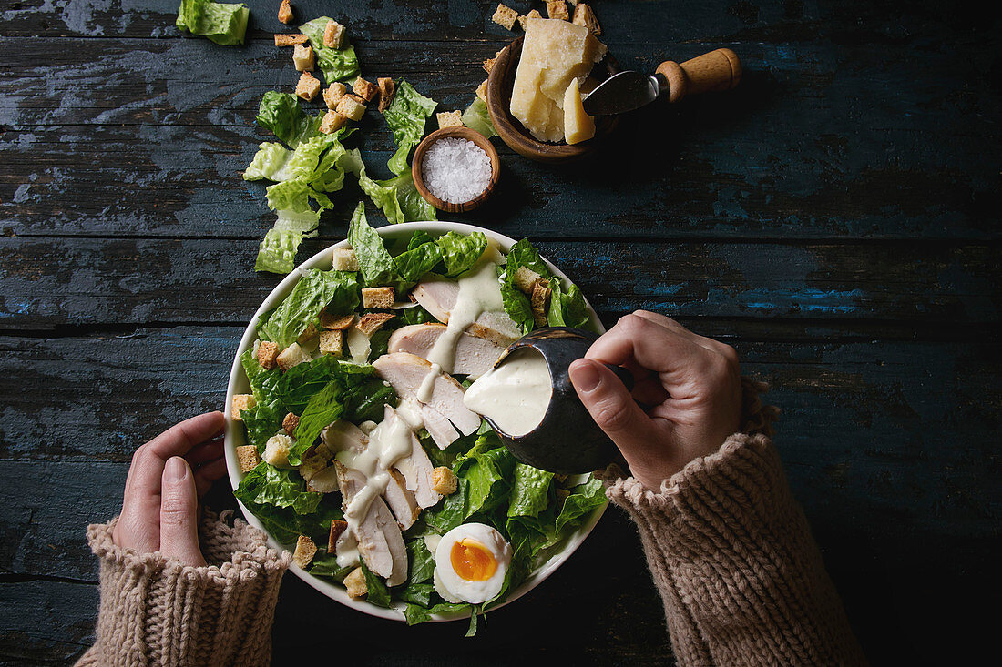 Female hands powring dressing to Classic Caesar salad with chicken breast in white ceramic plate