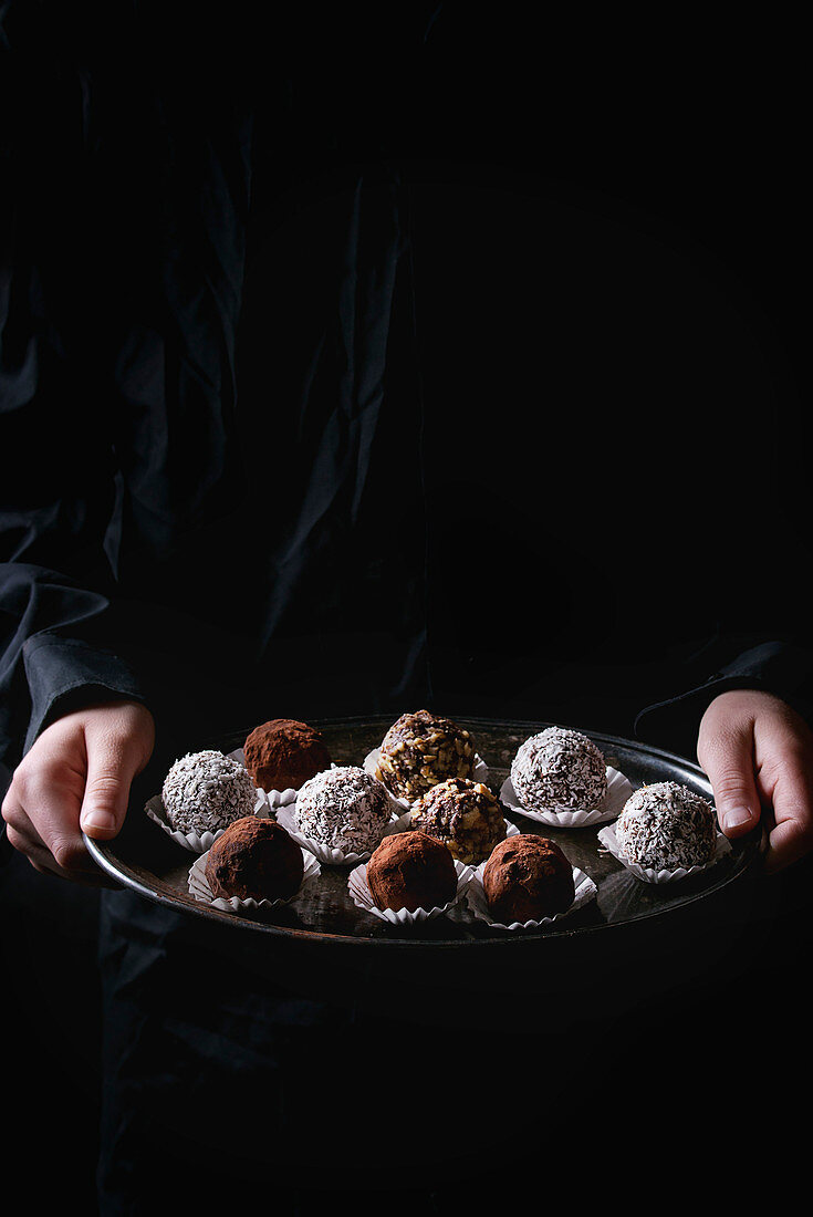 Variety of homemade dark chocolate truffles with cocoa powder, coconut, walnuts on vintage tray in kid's hands