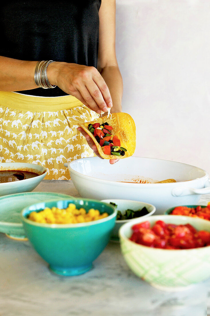 A woman making Black Bean Vegetable Enchiladas with home made enchilada sauce
