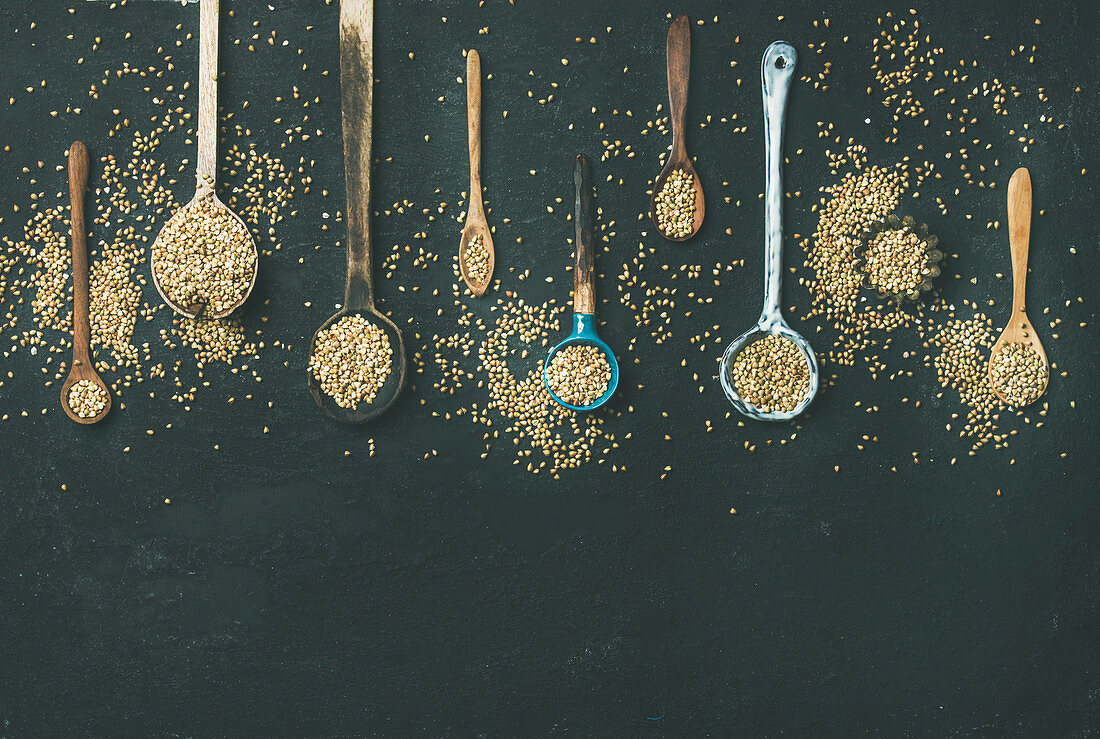 Various old vintage kitchen spoons full of green uncooked buckwheat grains over black stone background