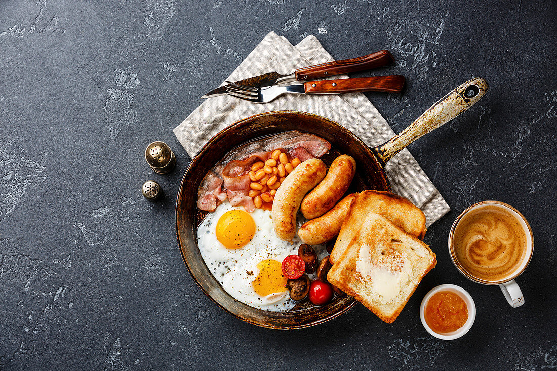 English breakfast in cooking pan with fried egg, sausage, bacon, beans, toast and coffee on dark background