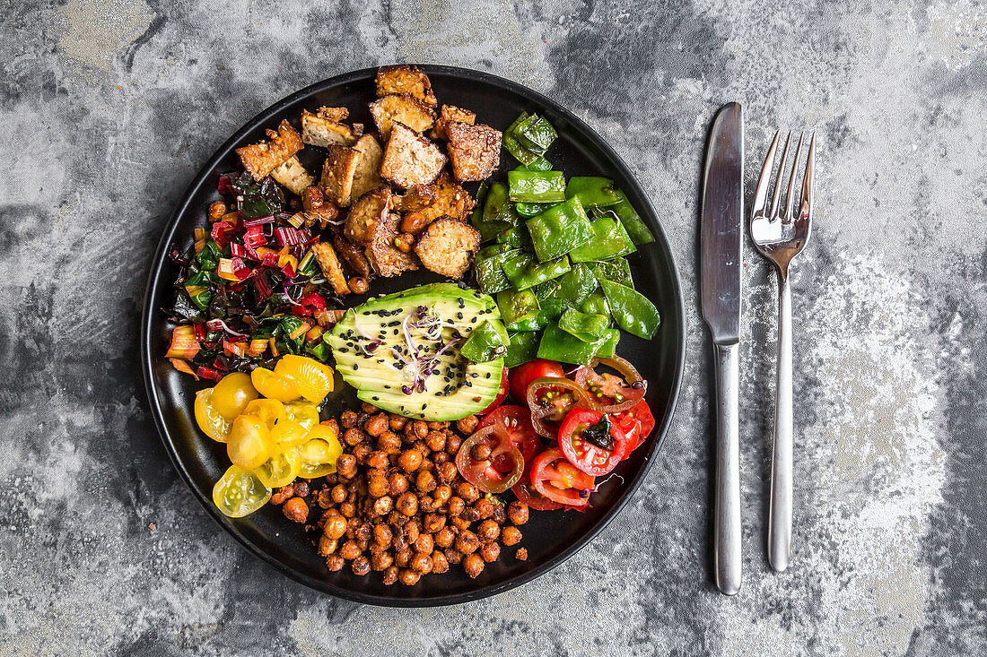 A salad plate with smoked tofu, chard, chickpeas, avocado, black sesame, tomatoes, mangetout and sprouts