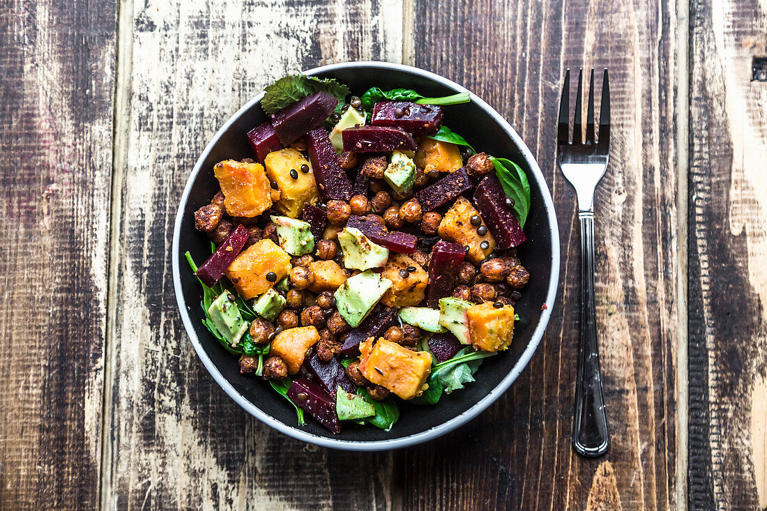 A superfood salad with avocado, beetroot, roasted chickpeas, sweet potato, beluga lentils and spinach