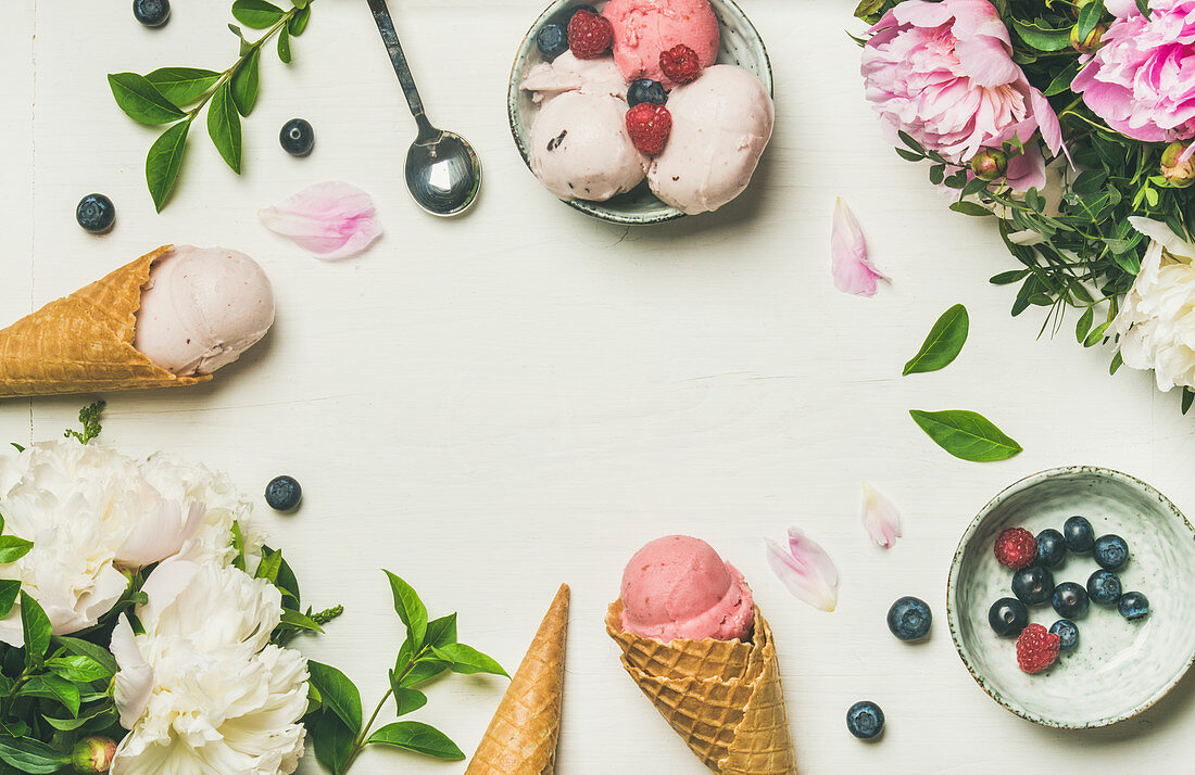 Pink strawberry and coconut ice cream scoops, sweet cones and peony flowers bouquet over white background