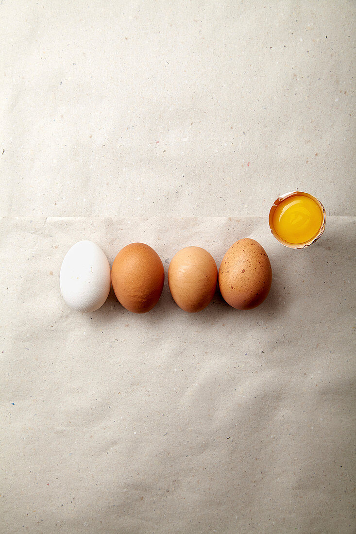 Four chicken eggs of different natural tint with one egg yolk on paper sheet