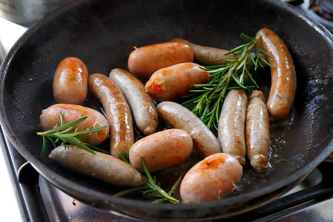Various sausages with rosemary in a pan