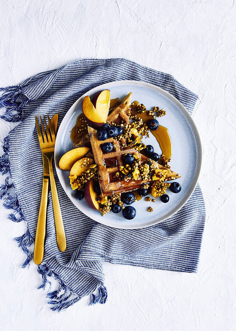 Healthy and light glutin free blueberry waffles with buckweat and nut turmeric muesli, golden peaches, fresh blueberrys and maple syrup