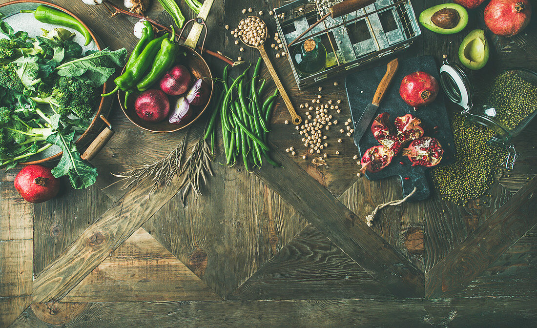 Winter vegetarian, vegan food cooking ingredients, seasonal vegetables and fruits, beans, cereals, kitchen utencils, dried flowers, olive oil over wooden background