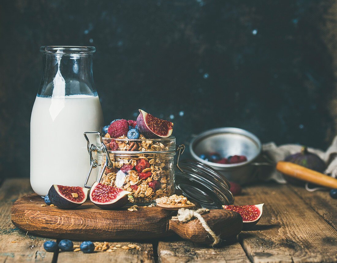 Healthy vegan breakfast, oatmeal granola with bottled almond milk, fresh fruit and berries over wooden table background, copy space