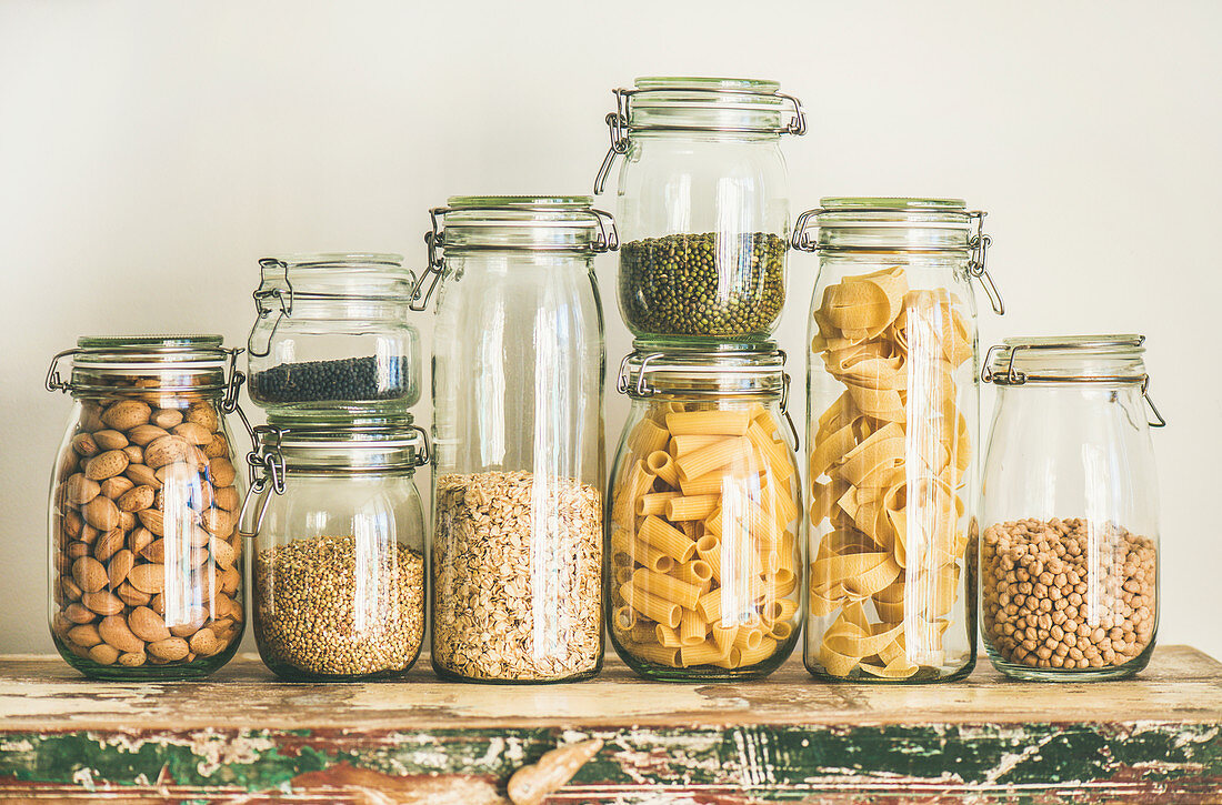 Various uncooked cereals, grains, beans and pasta for healthy cooking in glass jars on wooden table, white background
