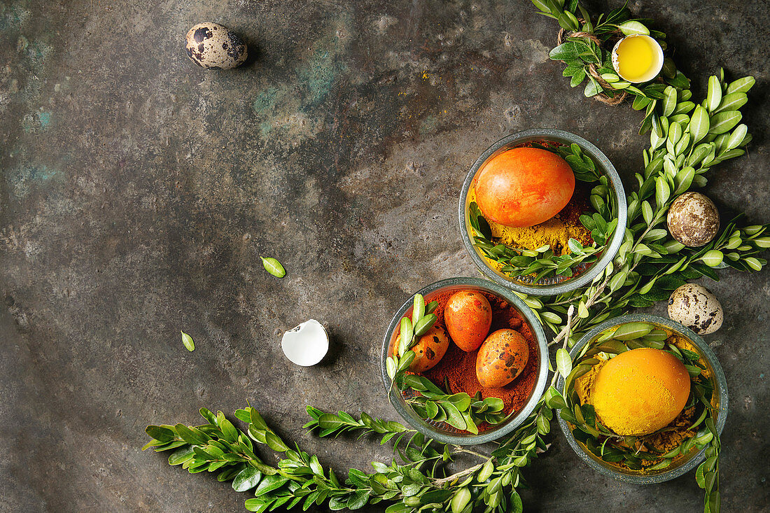 Colored yellow orange eggs in spices with quail eggs, yolk and green branches